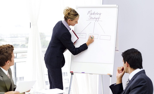 Businesswoman Writing on White Board and Businessman at Table