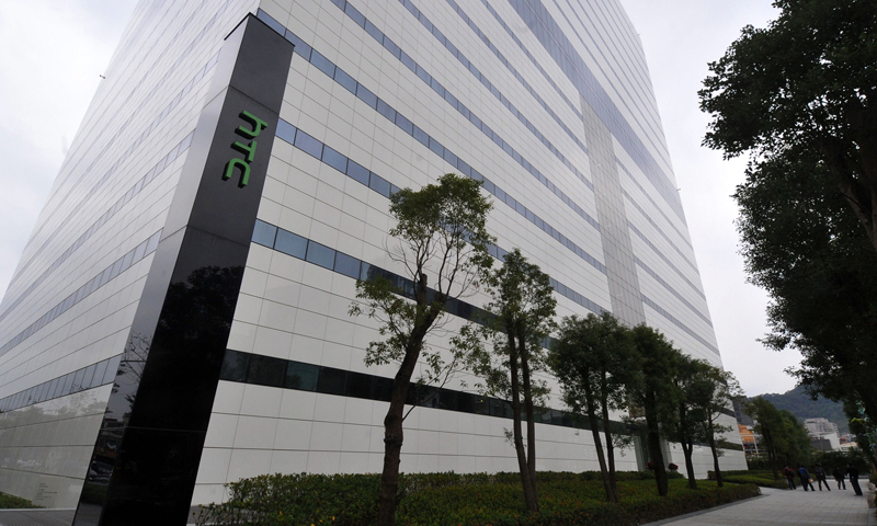 """People walk past a building of Taiwan's HTC during as a press conference takes place to release their 2013 corporate image advertising in New Taipei City on December 31, 2012. Taiwan's HTC unveiled a new smartphone  """"HTC butterfly"""" boasting a higher resolution display than iPhone5 on the island on December 11, 2012.  AFP PHOTO / Mandy CHENG"""