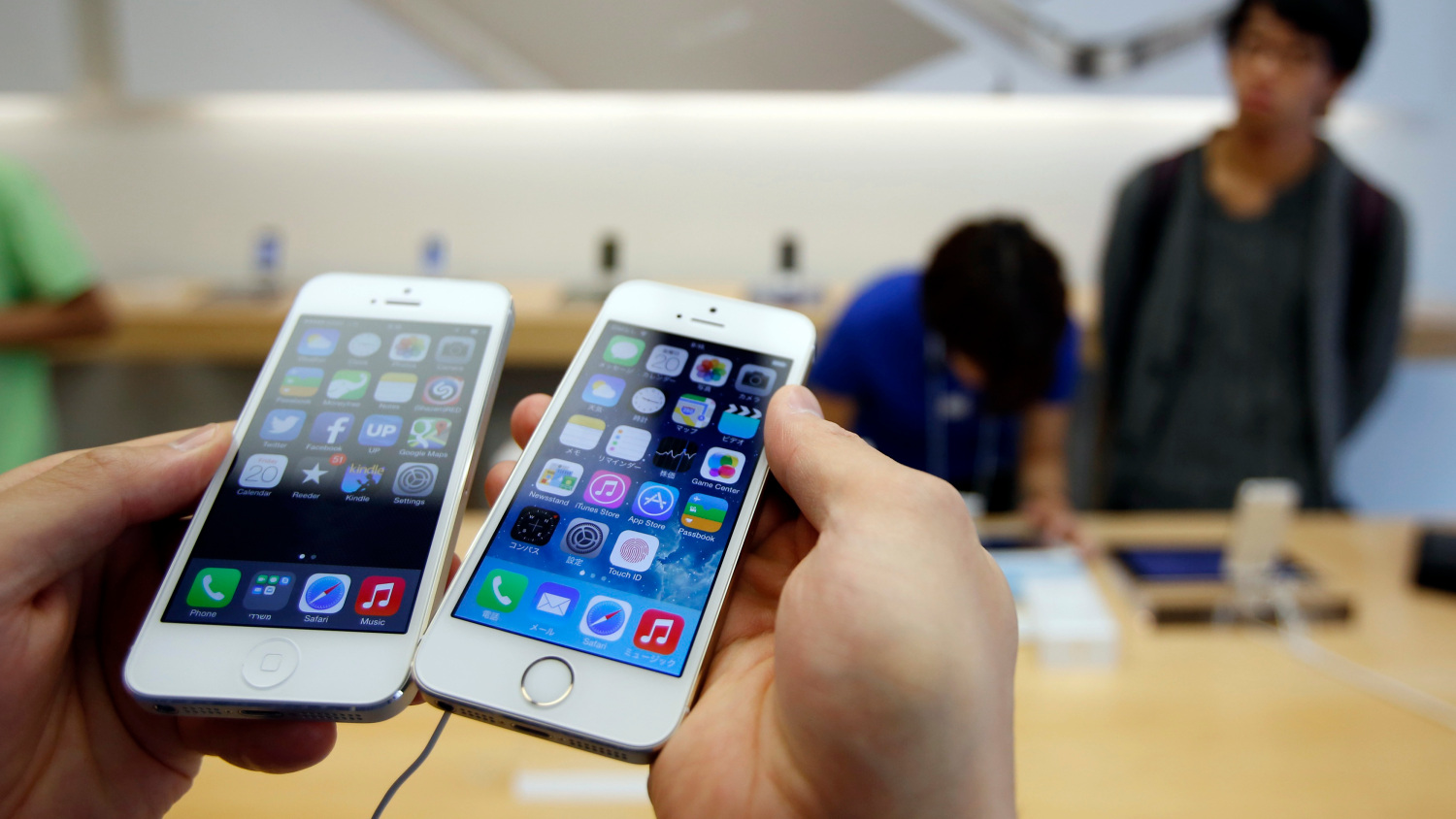 A man holds a new Apple iPhone 5S next to his iPhone 5 at an Apple Store at Tokyo's Ginza shopping district