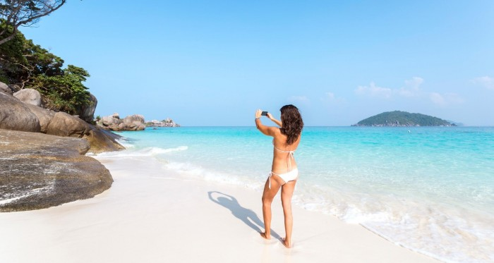 Woman in bikini taking photo of a beach with smartphone
